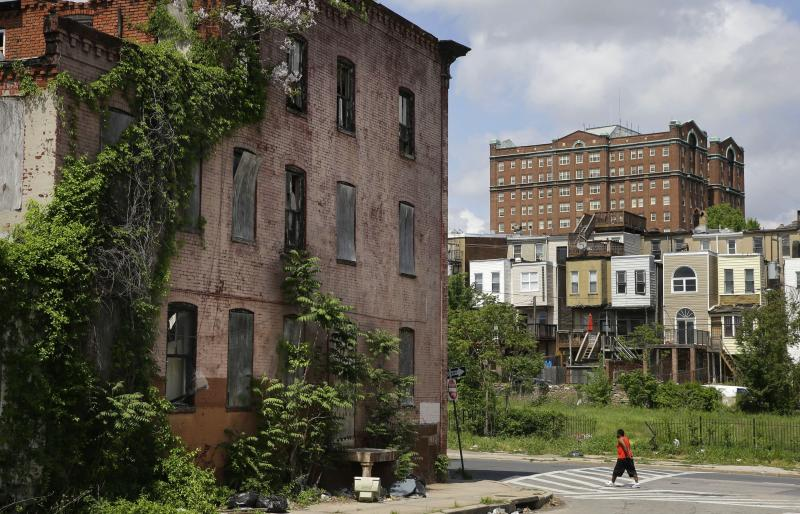 FILE-In this May 9, 2015 file photo, a man walks past a blighted building in the Penn-North neighborhood of Baltimore, with a residential tower in the Reservoir Hill neighborhood in the background at top right. New annual estimates from the U.S. Census Bureau show that Baltimore is continuing to shed inhabitants. Census data released Thursday, April 18, 2019 shows that Maryland's biggest city lost an estimated 7,346 citizens during the 12 months that ended July 1. (AP Photo/Patrick Semansky, File)