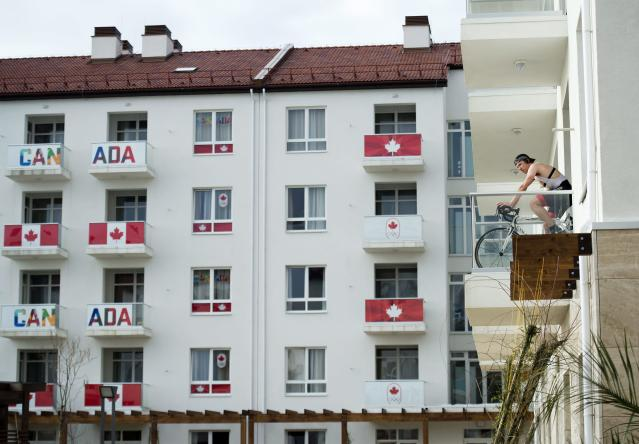 Canadian speed skater Mathieu Giroux trains on a bicycle on his room's balcony at the Canadian athletes village before the 2014 Sochi Winter Olympics in Sochi, Russia on Tuesday, Feb. 4, 2014. (AP Photo/The Canadian Press, Nathan Denette)