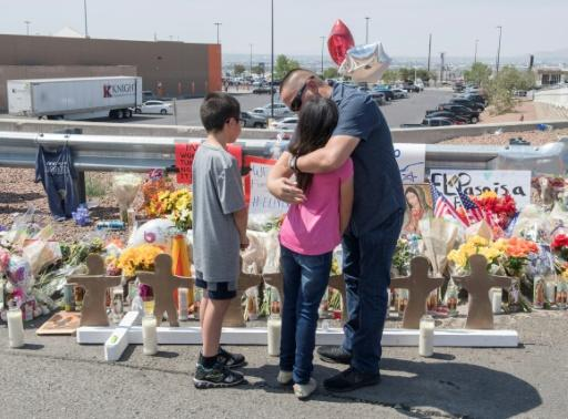 Members of the Soto family embrace beside a makeshift memorial after the shooting that left 22 people dead at the Cielo Vista Mall WalMart in El Paso, Texas, on August 5, 2019