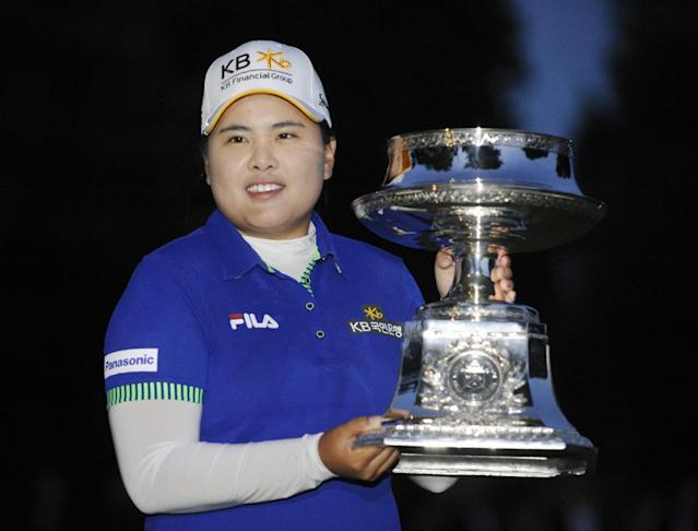 Inbee Park holds the championship trophy after she won the Wegmans LPGA golf tournament in Pittsford, N.Y., Sunday, Aug. 17, 2014. Park successfully defended her title in the LPGA Championship, beating Brittany Lincicome with a par on the first hole of a playoff Sunday to end the United States' major streak at three. (AP Photo/Gary Wiepert)