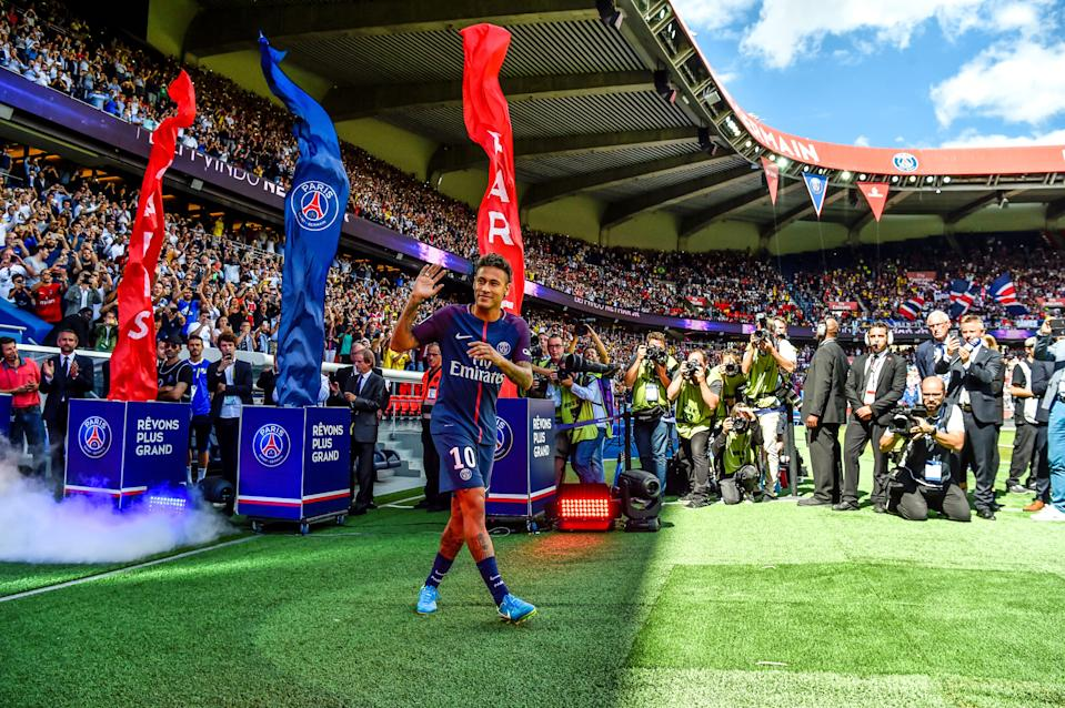 Paris Saint-Germain's Brazilian forward Neymar gestures as his arrives during his presentation to the fans at the Parc des Princes stadium in Paris on August 5, 2017.  Brazil superstar Neymar will watch from the stands as Paris Saint-Germain open their season on August 5, 2017, but the French club have already clawed back around a million euros on their world record investment. Neymar, who signed from Barcelona for a mind-boggling 222 million euros ($264 million), is presented to the PSG support prior to his new team's first game of the Ligue 1 campaign against promoted Amiens. / AFP PHOTO / ALAIN JOCARD        (Photo credit should read ALAIN JOCARD/AFP/Getty Images)