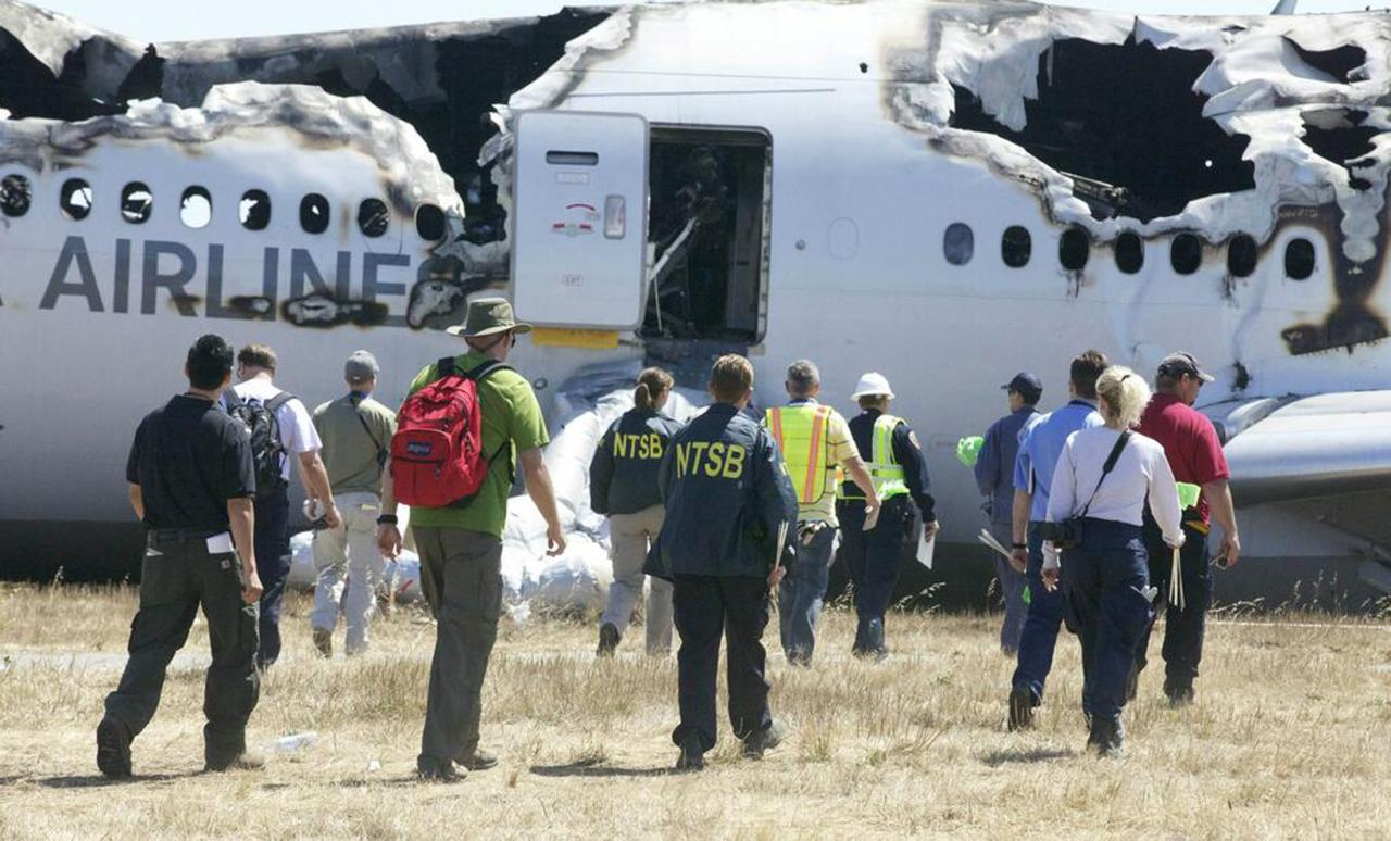 U.S. National Transportation Safety Board (NTSB) investigators work at the scene of the Asiana Airlines Flight 214 crash site at San Francisco International Airport in San Francisco, California, in this handout file photo released on July 7, 2013. U.S. safety investigators are looking closely at whether an over-reliance on autopilot systems in modern aircraft has degraded human flying skills, increasing the risk of accidents. At a two-day hearing that starts on December 10, 2013, the NTSB will examine if cockpit complacency caused the Asiana Airlines Inc's jetliner with 307 people aboard to crash land at San Francisco International Airport in July, killing three and injuring more than 180. REUTERS/NTSB/Handout/Files (UNITED STATES - Tags: TRANSPORT DISASTER) ATTENTION EDITORS - FOR EDITORIAL USE ONLY. NOT FOR SALE FOR MARKETING OR ADVERTISING CAMPAIGNS. THIS IMAGE HAS BEEN SUPPLIED BY A THIRD PARTY. IT IS DISTRIBUTED, EXACTLY AS RECEIVED BY REUTERS, AS A SERVICE TO CLIENTS