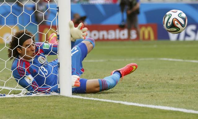 Mexico's goalkeeper Guillermo Ochoa saves the ball against Brazil's Neymar during their 2014 World Cup Group A soccer match at the Castelao arena