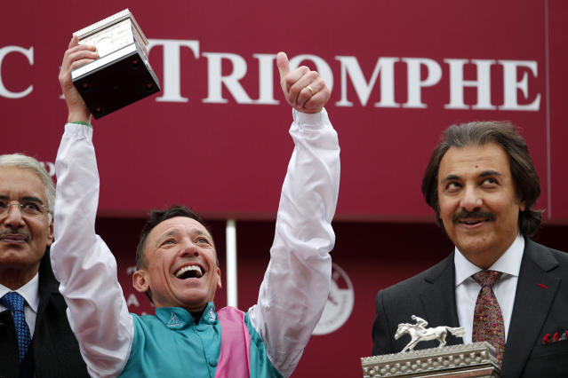 Italian Lanfranco Dettori riding British horse Enable, celebrates with the trophy after winning the Qatar Prix de l'Arc de Triomphe horse race at the Longchamp horse racetrack, outskirts of Paris, France, Sunday, Oct. 7, 2018. (AP Photo/Francois Mori)