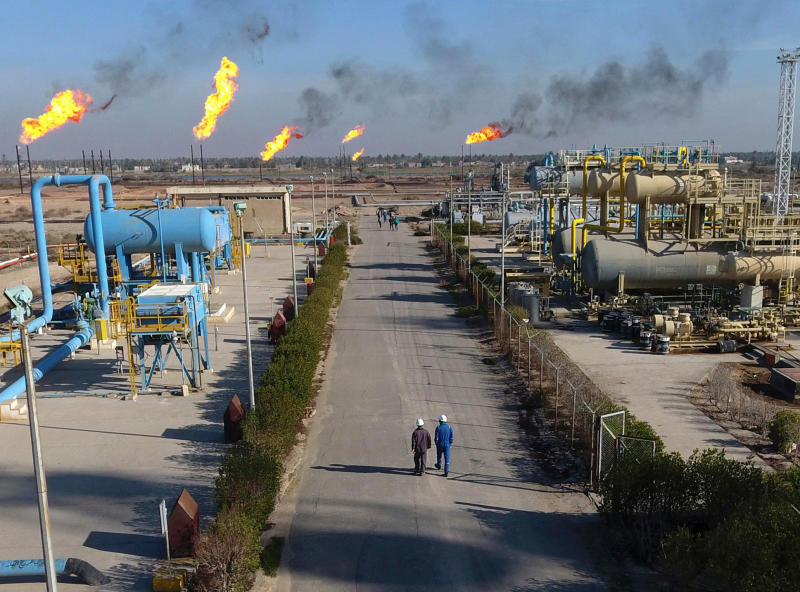 FILE - In this Thursday Jan. 12, 2017 file photo, workers walk in the Nihran Bin Omar field north near Basra, Iraq. An Iraqi oil official says employees of energy giant Exxon Mobil have started evacuating an oil field in the southern province of Basra, amid rising tensions between the United States and Iran. The first group left two days ago and another batch left early Saturday May 18, 2019. (AP Photo/Nabil al-Jurani, File)