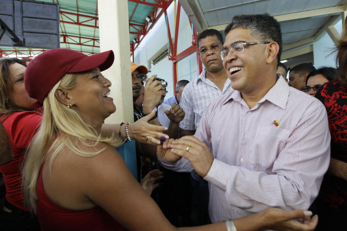 Elias Jaua, right, Venezuela's former Vice President and candidate for governor of Miranda state, greets supporters after casting his ballot at a polling station in Caracas, Venezuela, Sunday, Dec. 16, 2012. Venezuelans are choosing governors and state lawmakers in elections that have become a key test of whether President Hugo Chavez's movement can endure if the leader leaves the political stage. (AP Photo/Ariana Cubillos)