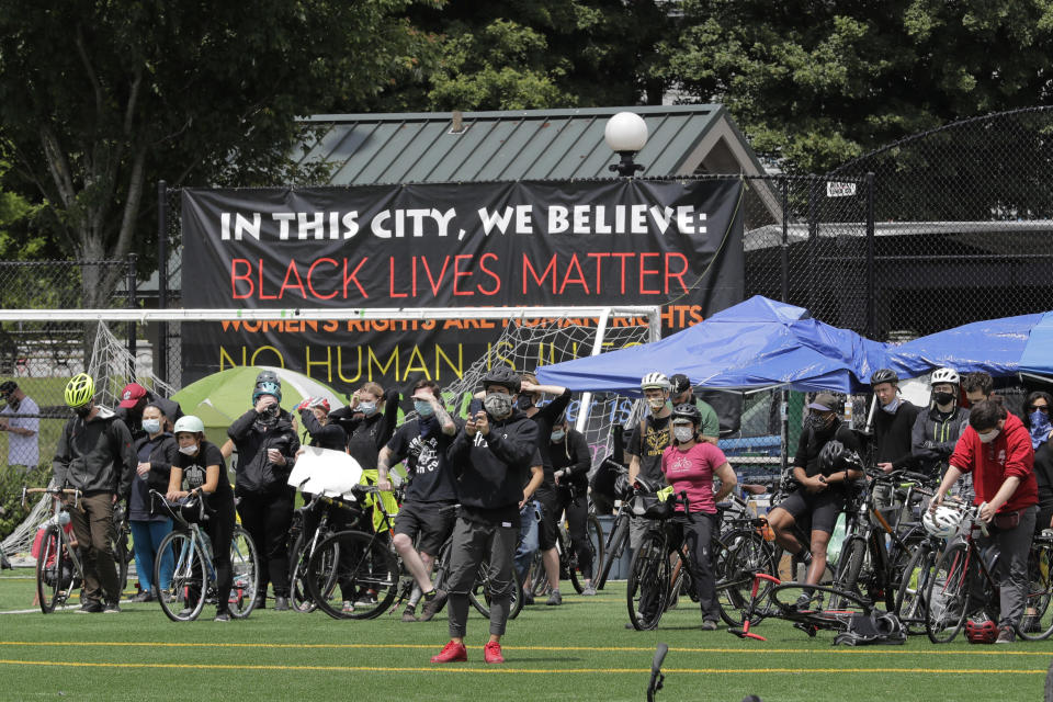 """Cyclists gather at Cal Anderson Park after taking part in the """"Ride for Justice,"""" Thursday, June 11, 2020, Seattle. People rode to the park and then took part in a rally to protest against police brutality and racial inequality. (AP Photo/Ted S. Warren)"""