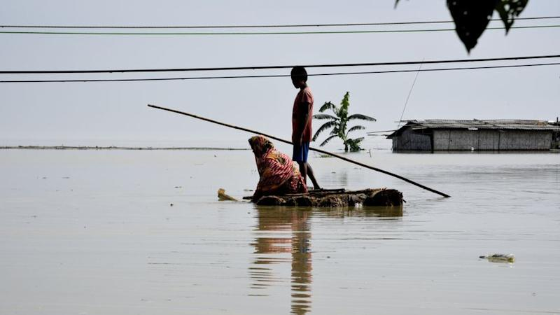 Villagers cross a flooded area on a makeshift raft, in Panikhaiti village, in Kamrup District, Assam, India on Tuesday, on July 14, 2020.