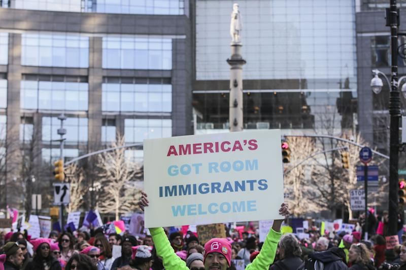 A demonstrator holds a sign that reads 'America's Got Room Immigrants Welcome' at Columbus Circle during the Women's March on New York City in New York, U.S., on Saturday, Jan. 20, 2018. One year after the inauguration of President Donald Trump, thousands of people will again gather to protest for equal rights at the 2018 Women's March. Photographer: Jeenah Moon/Bloomberg via Getty Images