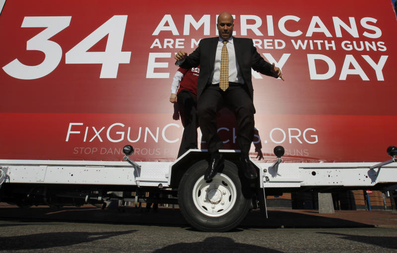 Newark Mayor Cory Booker leaps from the wheel cover of a mobile billboard after taking photos on it during part of the FixGunChecks.org Truck tour stop, Wednesday, Feb. 16, 2011, in Newark, N.J. The truck will be driven across the nation as part of the Mayors Against Illegal Guns which was launched by New York City Mayor Michael R. Bloomberg Wednesday. Its purpose will be to draw public attention to the deadly problems in the nation's gun background check system. (AP Photo/Julio Cortez)