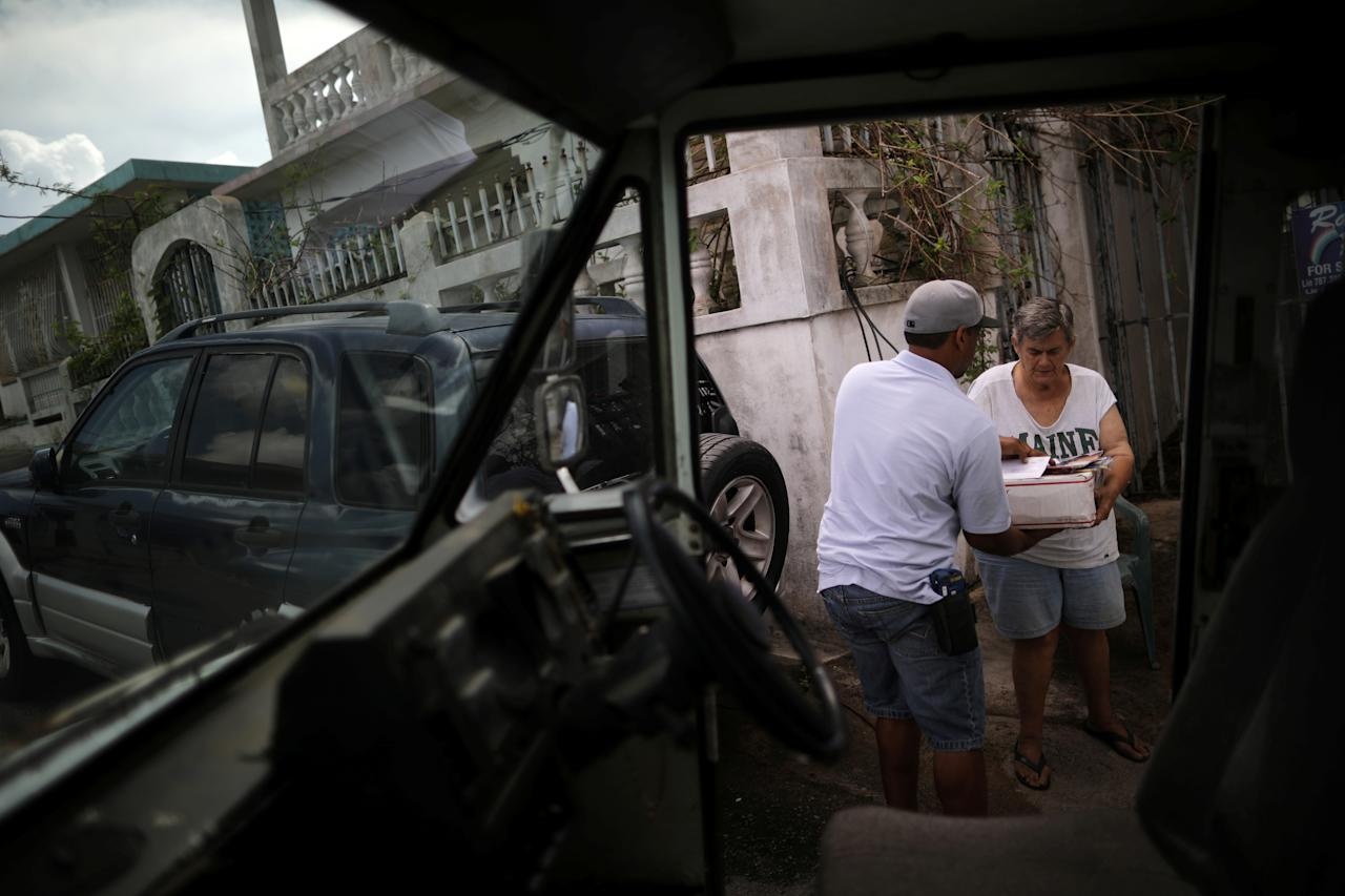 <p>Luis Menendez, a mail man for the U.S. Postal Service, delivers mail at an area affected by Hurricane Maria in the island of Vieques, Puerto Rico, Oct. 7, 2017. (Photo: Carlos Barria/Reuters) </p>