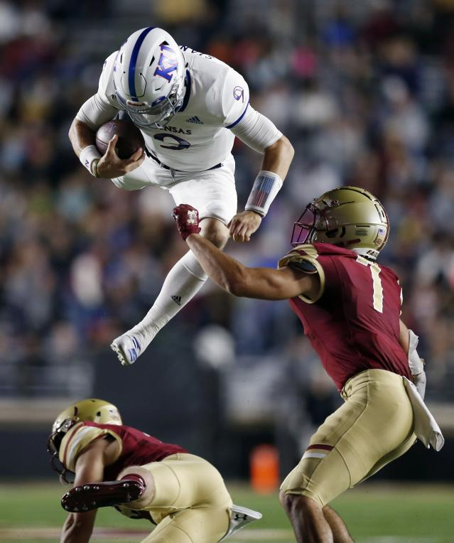 Kansas quarterback Carter Stanley (9) jumps over Boston College defensive back Nolan Borgersen, bottom, during the first half of an NCAA college football game in Boston, Friday, Sept. 13, 2019. (AP Photo/Michael Dwyer)