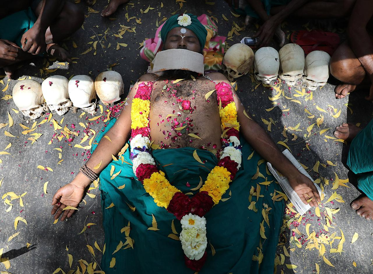 <p>An Indian farmer from South Indian Rivers Interlinking Farmers Association plays dead near human skulls claiming they belong to farmers who died in the past in Tamilnadu during a protest and hunger strike in New Delhi, India, March 25, 2017. Hundreds of farmers continuing their protest as they are demanding the formation of Cauvery river management committee and networking for all rivers by smart waterways project. (Photo: Rajat Gupta/EPA) </p>