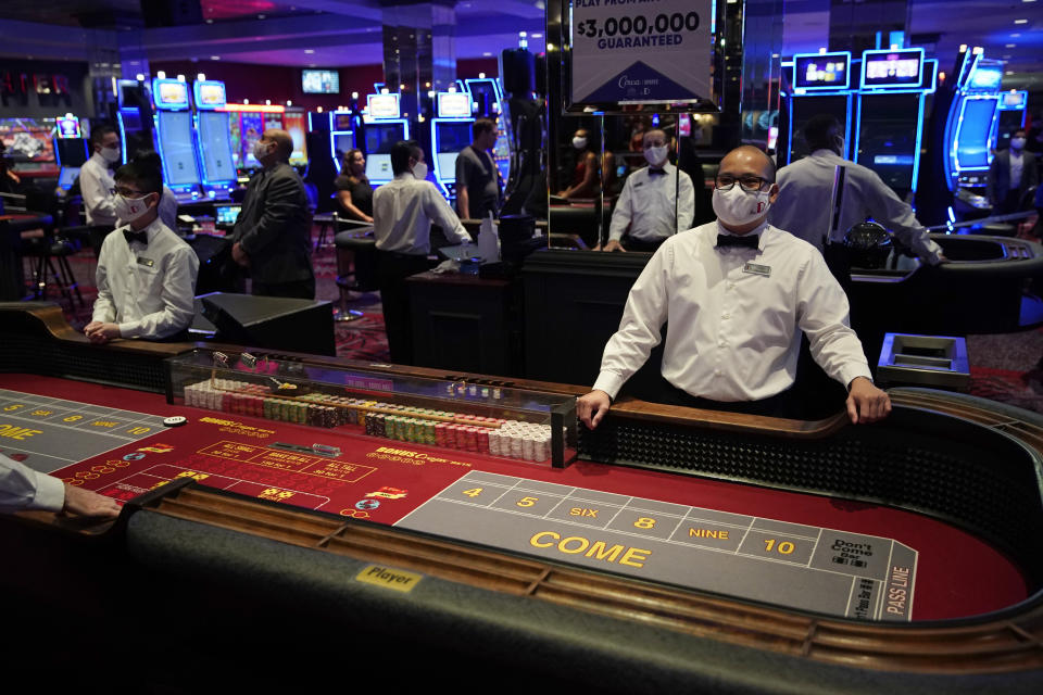 FILE - Dealers in masks wait for customers before the reopening of the D Las Vegas hotel and casino in Las Vegas, in this Wednesday, June 3, 2020, file photo. Governments and businesses are scrambling to change course following new federal guidance calling for the return of mask wearing in virus hot spots amid a dramatic spike in COVID-19 cases and hospitalizations nationwide. Nevada and Kansas City were among the locations that moved swiftly to re-impose indoor mask mandates following Tuesday's announcement from the Centers for Disease Control and Prevention. (AP Photo/John Locher, FIle)