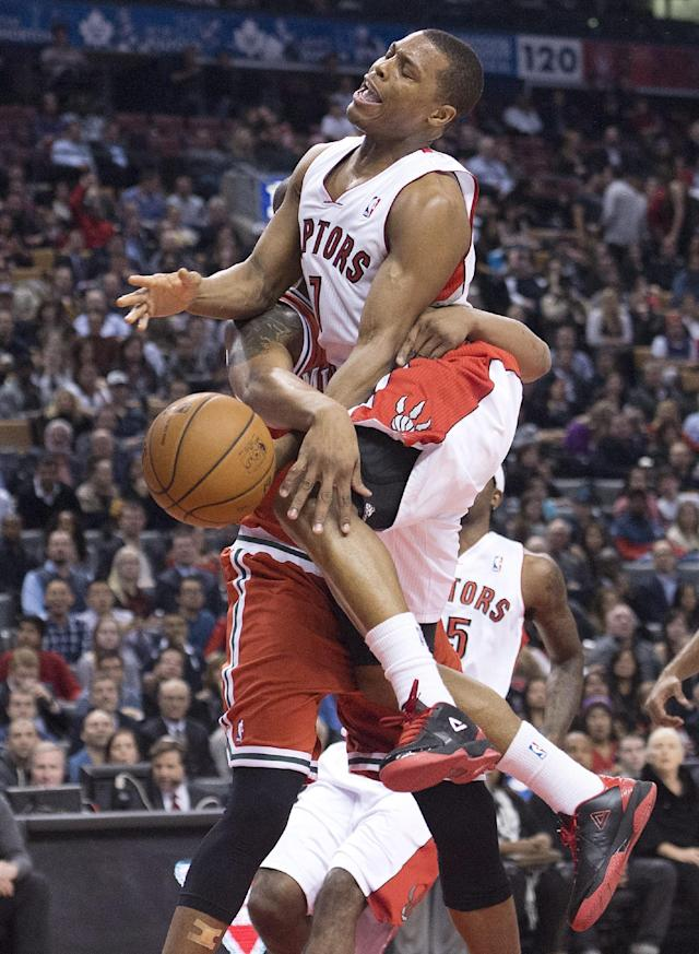 Toronto Raptors guard Kyle Lowry, front, gets fouled against Milwaukee Bucks forward Caron Butler during first half NBA basketball game in Toronto, Monday, Jan. 13, 2014. (AP Photo/The Canadian Press, Nathan Denette)