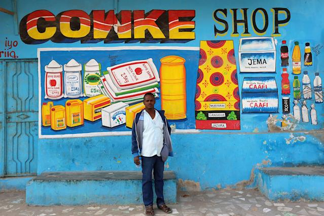 <p>Artist Muawiye Hussein Sidow, also known as Shik Shik, stands in front of a mural he painted on a shop wall in Mogadishu, Somali, July 21, 2017. (Photo: Feisal Omar/Reuters) </p>