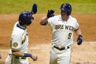 Milwaukee Brewers' Jedd Gyorko is congratulated by Christian Yelich after hitting a two-run home run during the eighth inning of a baseball game against the Minnesota Twins Tuesday, Aug. 11, 2020, in Milwaukee. (AP Photo/Morry Gash)