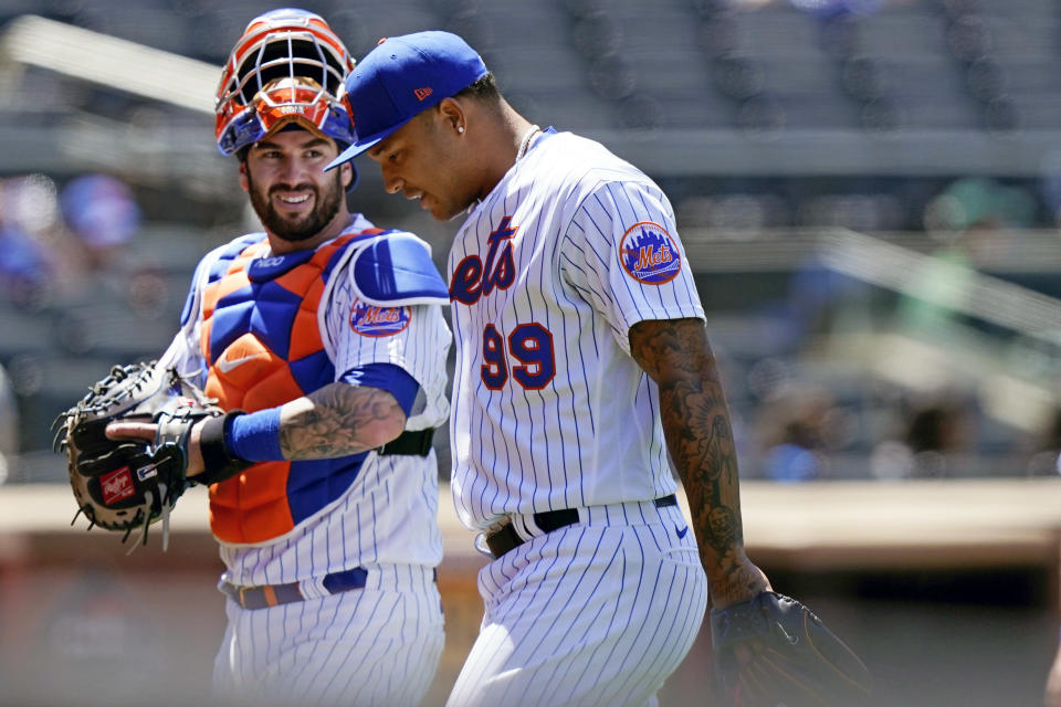 New York Mets catcher Tomas Nido, left, talks with Mets starting pitcher Taijuan Walker (99) during the Mets 7-1 victory over the Baltimore Orioles in a baseball game, Wednesday, May 12, 2021, in New York. (AP Photo/Kathy Willens)