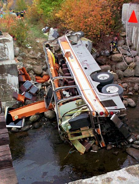 FILE - This Oct. 13, 1997, file photo, shows a bus on its side after it plunged into a ravine in Les Eboulements, northeast of Quebec City, killing 44 people. The bus crash was among Canada's deadliest accidents in the last 150 years, killing 44. Police say 50 people are presumed dead following a July 6, 2013, fiery oil train crash in Lac-Megantic, Quebec, making it Canada's worst railway crash in nearly 150 years. (AP Photo/Jacques Boissinot, File)