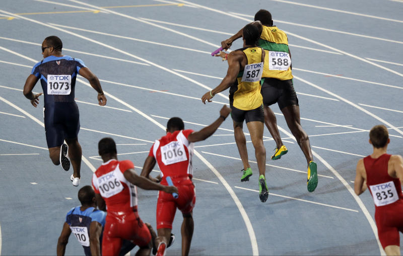 USA's anchor Walter Dix (1073)  runs as   his teammate Darvis Patton (1110) drops the baton in the Men's 4x100m relay final at the World Athletics Championships in Daegu, South Korea, Sunday, Sept. 4, 2011.  At top  Jamaica's Usain Bolt (588) and Yohan Blake (587) who took the gold.  (AP Photo/Kevin Frayer)