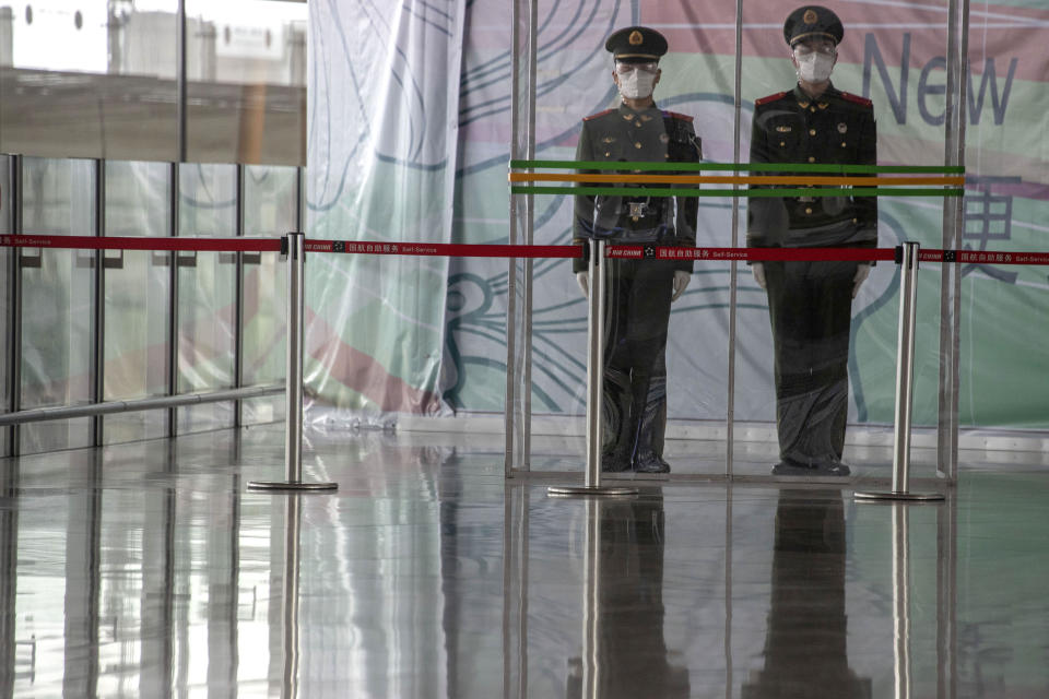 "FILE - In this March 12, 2020, file photo, Chinese paramilitary policemen stand on duty behind a barrier at the Capital International Airport terminal 3 in Beijing. President Donald Trump has repeatedly credited his February ban on travelers from mainland China as his signature move against the advance of the coronavirus pandemic -- a ""strong wall"" that allowed only U.S. citizens inside, he boasted in May. But Trump's wall was more like a sieve. Exempted were thousands of residents of the Chinese territories of Hong Kong and Macau. (AP Photo/Ng Han Guan, File)"