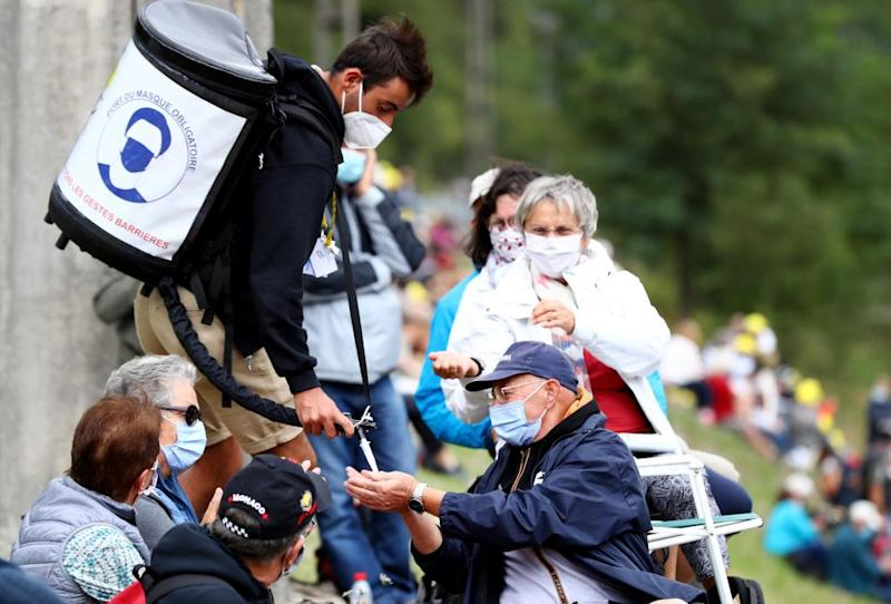 Hand sanitiser is distributed to fans ahead of the 9th Stage from Pau to Laruns.
