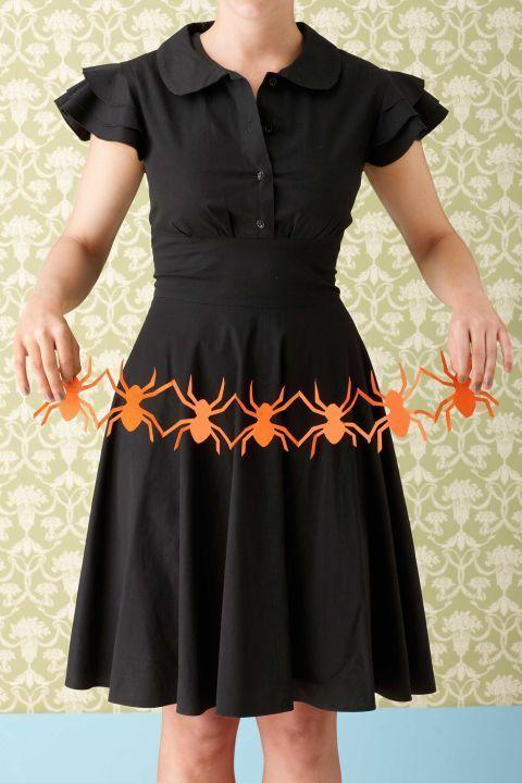 """<p>Using <a href=""""https://www.countryliving.com/diy-crafts/how-to/a3048/halloween-templates-1009/"""" rel=""""nofollow noopener"""" target=""""_blank"""" data-ylk=""""slk:our templates"""" class=""""link rapid-noclick-resp"""">our templates</a> for spiders, bones, and skulls, anyone (even the little ones) can help make some creepy decor. </p><p><strong>To make: Step 1:</strong> Cut a 5""""W x 18""""L strip from a 12""""W x 18""""L sheet of construction paper. Measure in three inches from one of the five-inch ends and mark. From there, measure and mark four more times.</p><p><strong>Step 2:</strong> Fold paper at the first mark. Then flip over and fold again at the next mark. Keep flipping and folding, making an accordion shape.</p><p><strong>Step 3:</strong> Print the template of your choice and cut as directed.</p><p><strong>Step 4:</strong> Center it atop the folded paper, and trace around the shape with a pencil.</p><p><strong>Step 5:</strong> Carefully cut out the shape, going through all the layers of folded paper, and unfold to reveal. To create a longer row, repeat steps and adhere garlands together with tacky glue. </p>"""