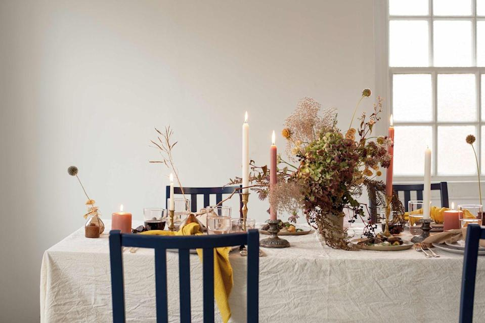 """<p>Bring the outside in for a nature-themed setting, rich in earthy shades. This table, created by sustainable event designers Luminosa, hints at warm winter sun with dried floral arrangements and organic textures</p><p>Organic calico <strong>tablecloth</strong>, from £80; naturally dyed cotton <strong>napkins</strong>, from £14 each, all Luminosa (<u><a href=""""https://www.luminosa-events.com/portfolio"""" rel=""""nofollow noopener"""" target=""""_blank"""" data-ylk=""""slk:luminosa-events.com"""" class=""""link rapid-noclick-resp"""">luminosa-events.com</a></u>). '365+' 30cl <strong>glasses</strong>, £3 for six, Ikea (<u><a href=""""https://www.ikea.com/gb/en/p/ikea-365-glass-clear-glass-70278358/"""" rel=""""nofollow noopener"""" target=""""_blank"""" data-ylk=""""slk:ikea.com"""" class=""""link rapid-noclick-resp"""">ikea.com</a></u>). Hand-built <strong>dinner plates</strong>, £36 each; hand-built <strong>side </strong><strong>plates</strong>, £28 each, Olivia Fiddes (<u><a href=""""http://www.oliviafiddes.com/faye-toogood-x-olivia-fiddes"""" rel=""""nofollow noopener"""" target=""""_blank"""" data-ylk=""""slk:oliviafiddes.com"""" class=""""link rapid-noclick-resp"""">oliviafiddes.com</a></u>). For similar antique silver <strong>cutlery</strong>, try Baileys (<u><a href=""""https://baileyshome.com/collections/tableware/products/brushed-stainless-steel-cutlery?variant=34492575318061"""" rel=""""nofollow noopener"""" target=""""_blank"""" data-ylk=""""slk:baileyshome.com"""" class=""""link rapid-noclick-resp"""">baileyshome.com</a></u>). For similar antique brass <strong>candlesticks</strong>, try Vinterior (<u><a href=""""https://www.vinterior.co/"""" rel=""""nofollow noopener"""" target=""""_blank"""" data-ylk=""""slk:vinterior.co"""" class=""""link rapid-noclick-resp"""">vinterior.co</a></u>). Vintage <strong>chairs </strong>painted in 'Stiffkey Blue' <strong>paint</strong>, £62 for 2.5 litres, Farrow & Ball (<u><a href=""""https://www.farrow-ball.com/paint-colours/stiffkey-blue"""" rel=""""nofollow noopener"""" target=""""_blank"""" data-ylk=""""slk:farrow-ball.com"""" class=""""link rapid-noclick-resp"""">farrow-ball.com</a></u>). Fo"""