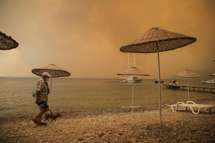A man walks with his dog on the beach of smoke-engulfed Mazi area as wildfires rolled down the hill toward the seashore, in Bodrum, Mugla, Turkey, Sunday, Aug. 1, 2021. More than 100 wildfires have been brought under control in Turkey, according to officials. The forestry minister tweeted that five fires are continuing in the tourist destinations of Antalya and Mugla. (AP Photo/Emre Tazegul)