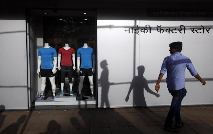 FILE - In this Saturday, Aug. 31, 2013, file photo, an Indian man walks in front of a factory outlet store in Mumbai, India. Despite a growing middle class, Indians have dumped 15 percent of their holdings in the five years after the financial crisis. (AP Photo/Rajanish Kakade, File)