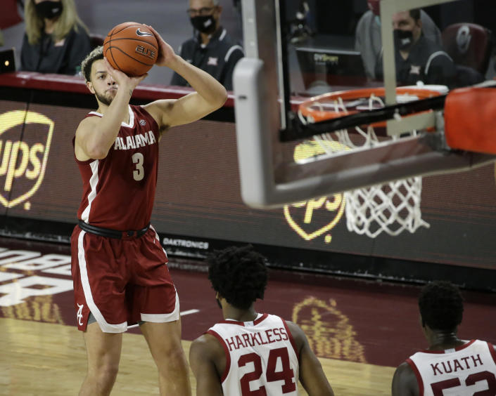 Alabama's Alex Reese (3) takes a shot against Oklahoma's Elijah Harkless (24) and Kur Kuath (52) during the first half of an NCAA college basketball game in Norman, Okla., Saturday, Jan. 30, 2021. (AP Photo/Garett Fisbeck)