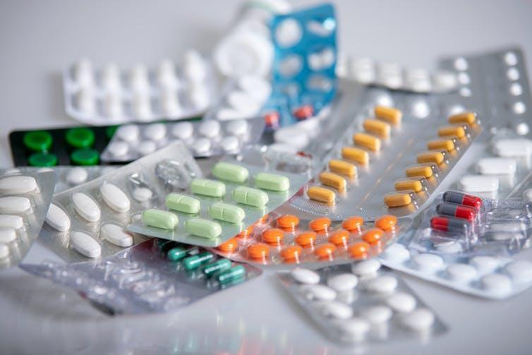 Various packets of coloured tablets on a table