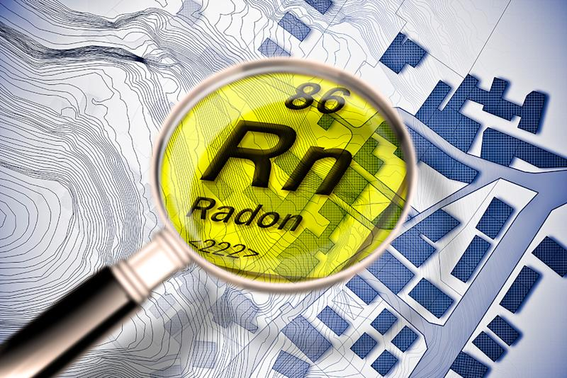 The dangerous radioactive radon gas in our cities - concept image with periodic table of the elements, magnifying lens and city map on background
