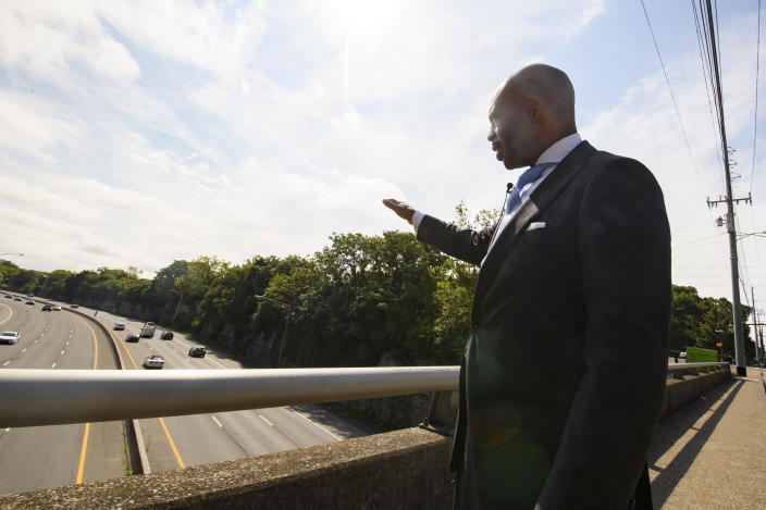 Tennessee State Rep. Harold Love, Jr. gestures toward an area he is supporting to expand a bridge and make a cap over I-40, Monday, July, 19, 2021, on the north side of Nashville, Tenn. Love Jr.'s father, a Nashville city councilman, was forced to sell his family home nearby, to make way for the highway, but put up a fight in the 1960s against the rerouting of Interstate 40 because he believed it would stifle and isolate Nashville's Black community. (AP Photo/John Amis)