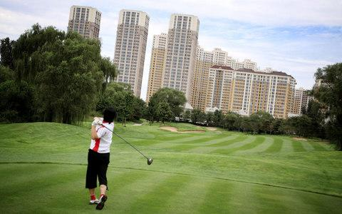 A golfer tees off at Huatang International Golf Club in Beijing - Credit: National Geographic Creative / Alamy Stock Photo