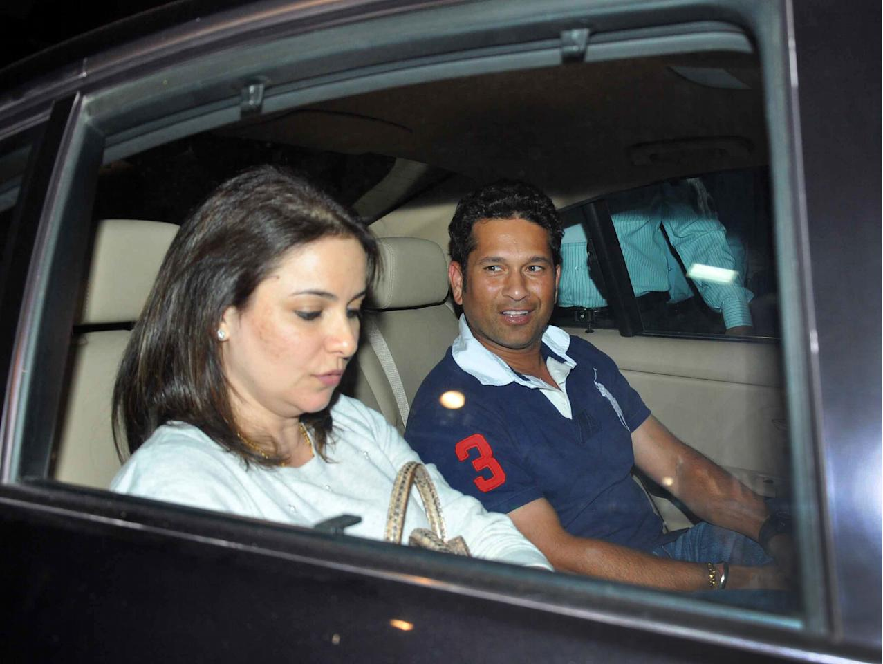 In this photograph taken on October 30, 2013, Indian cricketer Sachin Tendulkar (R) and his wife Anjali Tendulkar sit in a vehicle as they leave an airport in Jodhpur, after arriving to attend socialite Nita Ambani's 50th birthday celebrations. AFP PHOTO/STR        (Photo credit should read STRDEL/AFP/Getty Images)
