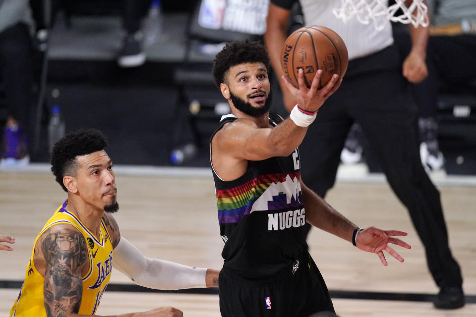 Denver Nuggets' Jamal Murray (27) scores past Los Angeles Lakers' Danny Green (14) during the second half of an NBA conference final playoff basketball game Thursday, Sept. 24, 2020, in Lake Buena Vista, Fla. The Lakers won 114-108. (AP Photo/Mark J. Terrill)
