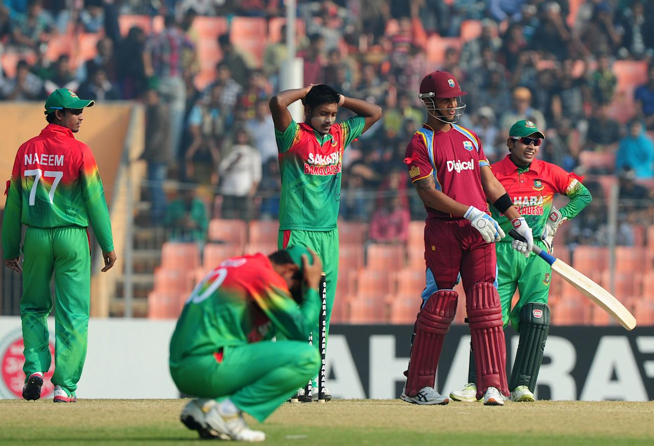 Bangladesh cricket captain Mushfiqur Rahim (R) and teammate Abul Hasan (C) react as West Indies batsman  Lendl Simmons (2R) looks on during the first one day international cricket match between Bangladesh and The West Indies at The Sheikh Abu Naser Stadium in Khulna on November 30, 2012.  AFP PHOTO/ Munir uz ZAMAN