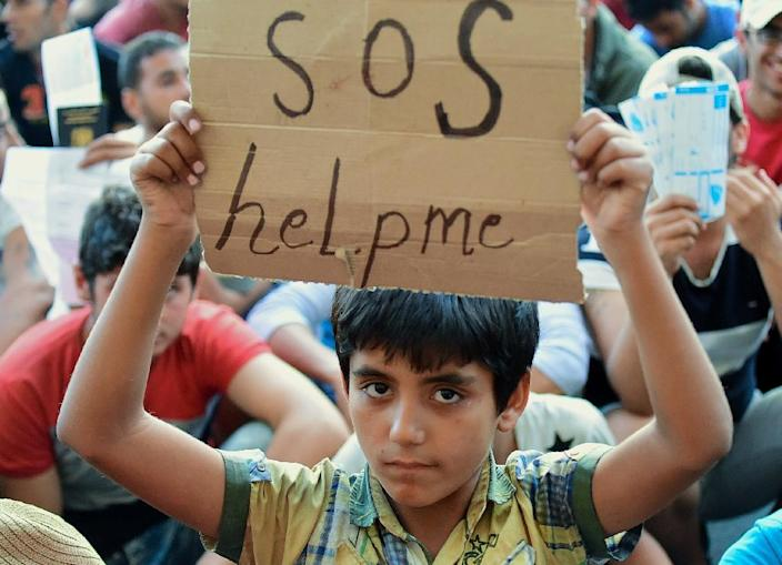 A migrant boy holds a sign reading 'SOS help me' as he sits with other migrants in front of the Keleti (East) railway station in Budapest on September 2, 2015 (AFP Photo/Attila Kisbenedek)