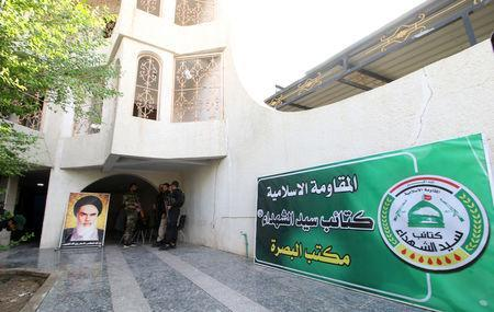 A poster of Iranian revolutionary leader Ayatollah Ruhollah Khomeini is seen outside the headquarters of a Shi'ite group Martyrs Movement in Basra, Iraq November 8, 2018. The text on the green banner reads 'Islamic Resistance, Kataib Sayyid al-Shuhada, Basra Office'. Picture taken November 8, 2018. REUTERS/Essam al-Sudani