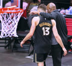 Atlanta Hawks interim head coach Nate McMillan, right, and guard Bogdan Bogdanovic walk off the court together after falling to the Milwaukee Bucks in Game 6 of the Eastern Conference finals in the NBA basketball playoffs Saturday, July 3, 2021, in Atlanta. (Curtis Compton/Atlanta Journal-Constitution via AP)