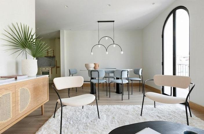 In the dining room, the Coco chairs by Gubi surround the Volà table designed by Noé Prades Studio with a Pholc light fixture hanging above it.