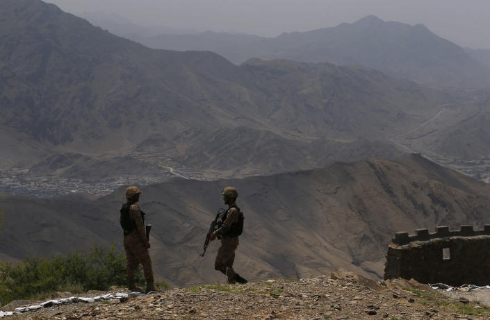 Pakistan Army troops observe the area from a hilltop post on the Pakistan Afghanistan border in Khyber district, Pakistan, Tuesday, Aug. 3, 2021. Pakistan's military said it completed 90 percent of the fencing along the border, vowing the remaining one of the most difficult tasks of improving the border management will be completed this summer to prevent any cross-border militant attack from both sides. (AP Photo/Anjum Naveed)