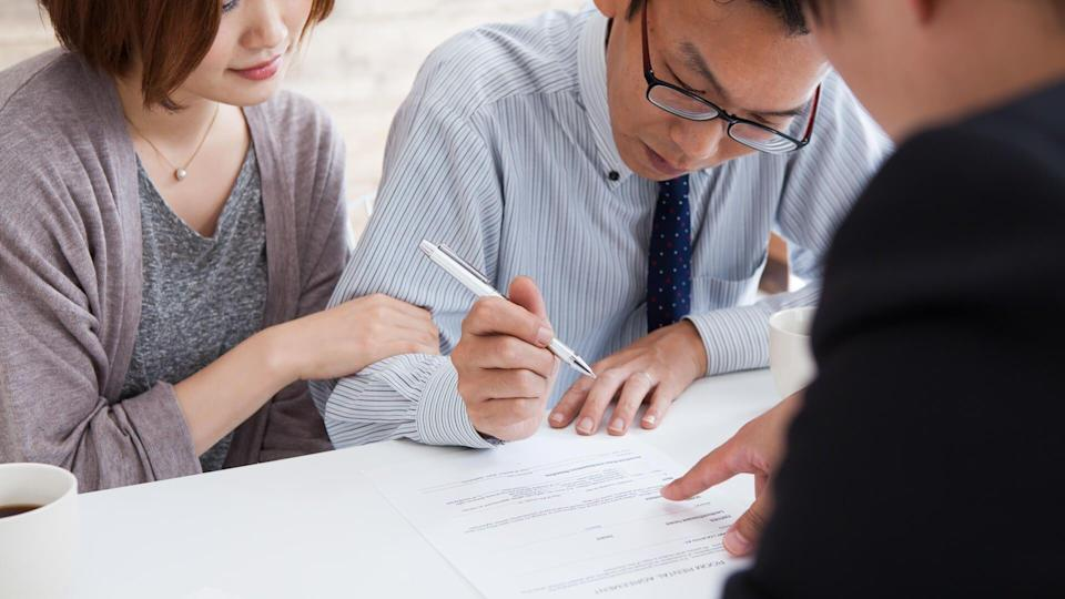 couple signing a real estate contract in real estate agency.