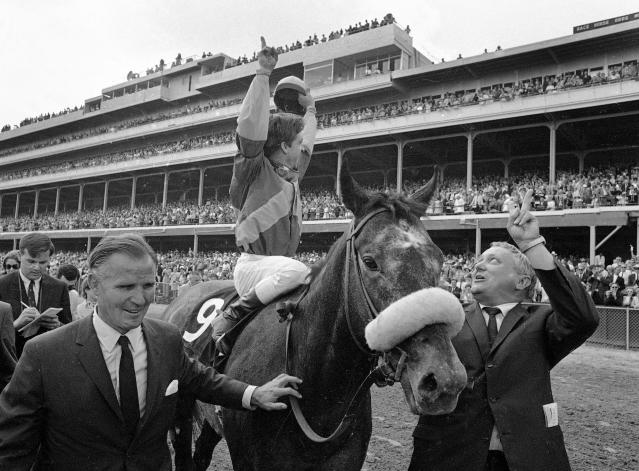 FILE - In this May 4, 1968 file photo, jockey Bob Ussery celebrates aboard Kentucky Derby winner Dancer's Image on his way to the winner's circle flanked by owner Peter Fuller, left, and trainer Louis C. Cavalaris Jr., right, at Churchill Downs in Louisville, Ky. Sent off as the 7-2 second choice, Dancer's Image rallied from last to win by 1 1/2 lengths over Forward Pass. The result was declared official, but Dancers Image was later disqualified after traces of phenylbutazone, known as bute, were found in Dancer's Image's post-race urinalysis. Dancer's Image was placed 14th and last; Forward Pass was declared the winner. (AP Photo/File)