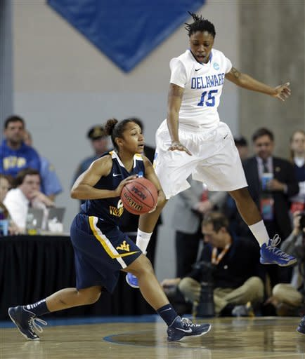 West Virginia guard Taylor Palmer, left, drives the ball as she is pressured by Delaware guard Akeema Richards during the first half of a first-round game in the women's NCAA college basketball tournament in Newark, Del., Sunday, March 24, 2013. (AP Photo/Patrick Semansky)