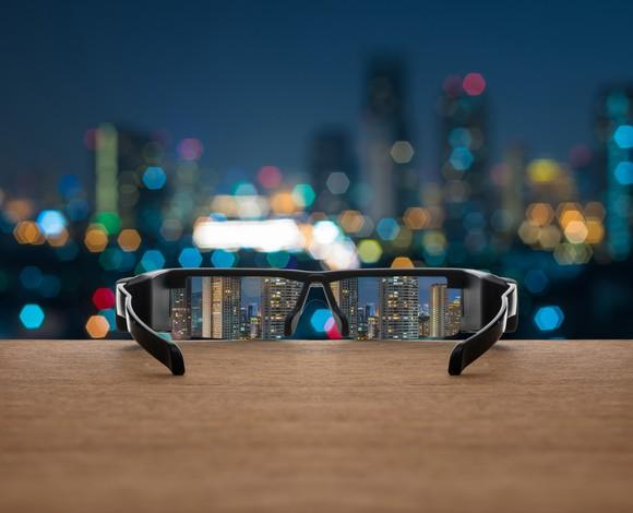 Augmented reality glasses sitting on a table, facing a night cityscape