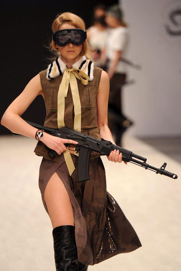 A model is seen holding a gun during designer Tatiana Efremova's show on November 5, 2016. (SERGEI GAPON/AFP/Getty Images)
