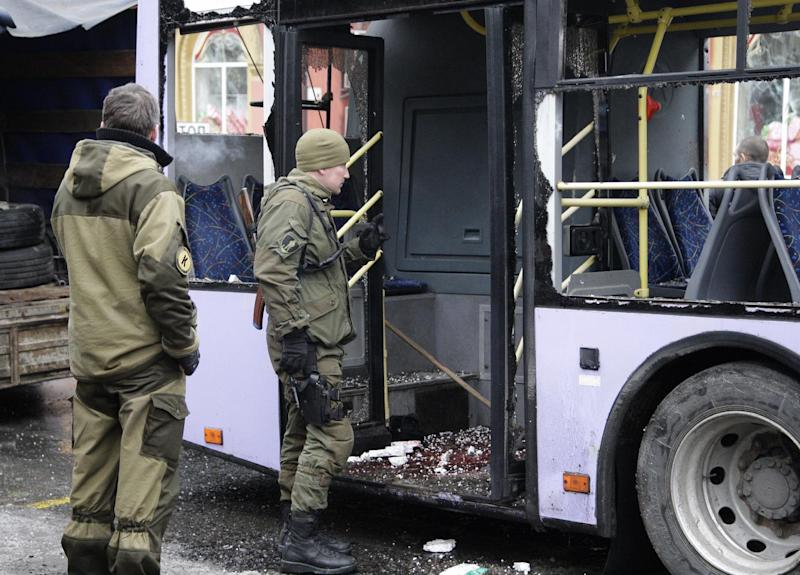 Pro-Russian rebels inspect a bus that was hit by shelling after fierce clashes near the eastern city of Donetsk, on January 22, 2015 (AFP Photo/Alexander Ermochenko)