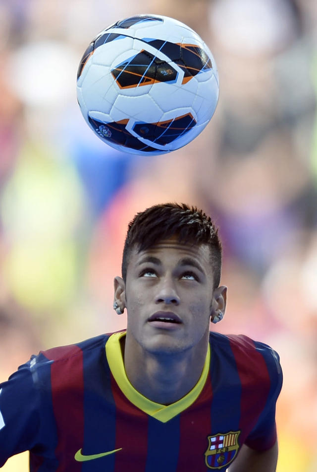 FILE - In this June 3, 2013 file photo, FC Barcelona's new signing, Neymar controls the ball during his official presentation at the Camp Nou stadium in Barcelona, Spain. As the player carrying Brazils hopes for a World Cup title at home, Neymar is expected to attract most of the attention at the Confederations Cup. After his high profile transfer to Barcelona, the scrutiny is only likely to increase. (AP Photo/Manu Fernandez, File)
